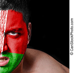Portrait of angry man with painted flag of Belarus