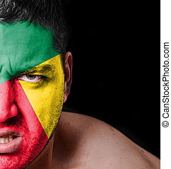 Portrait of angry man with painted flag of Benin