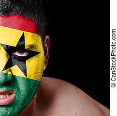 Portrait of angry man with painted flag of Ghana