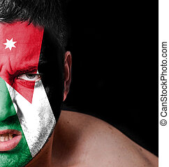 Portrait of angry man with painted flag of Jordan