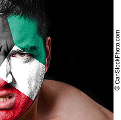 Portrait of angry man with painted flag of Kuwait
