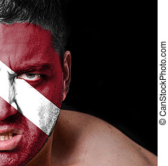 Portrait of angry man with painted flag of Latvia
