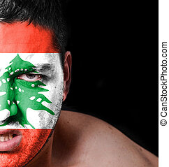 Portrait of angry man with painted flag of Lebanon