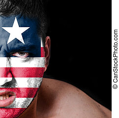 Portrait of angry man with painted flag of Liberia