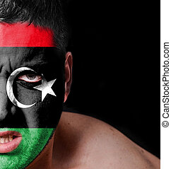 Portrait of angry man with painted flag of Libya