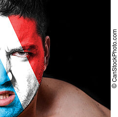 Portrait of angry man with painted flag of Luxembourg