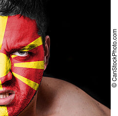 Portrait of angry man with painted flag of Macedonia
