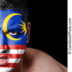 Portrait of angry man with painted flag of Malaysia