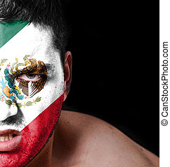 Portrait of angry man with painted flag of Mexico