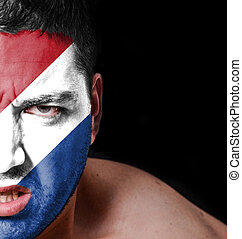 Portrait of angry man with painted flag of Netherlands