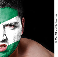 Portrait of angry man with painted flag of Nigeria