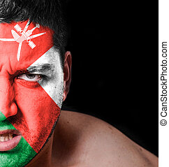 Portrait of angry man with painted flag of Oman