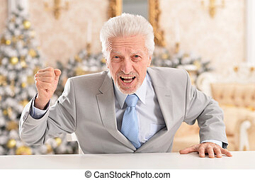 Portrait of angry senior businessman at table