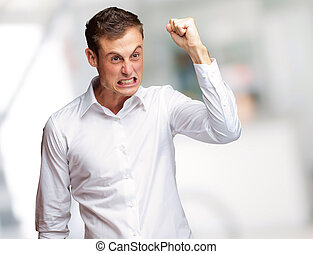 Portrait Of Angry Young Man Clenching His Fist, Outdoor