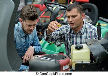 portrait of apprentice checking lawn mower