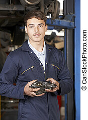 Portrait Of Apprentice Mechanic In Auto Repair Shop
