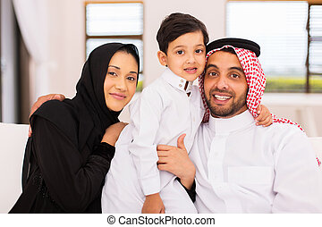 arabian couple with their son sitting on couch