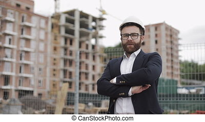 Portrait of architect man in business suit standing on the construction site with crossed hands looking at the camera. Outside, slow motion.