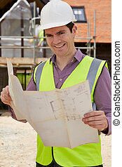 Portrait Of Architect On Building Site Looking At House Plans