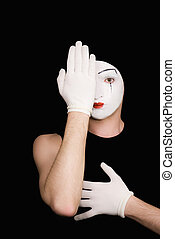 Portrait of artful peeping mime in white gloves