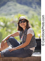 portrait of asian 40s years woman wearing straw hat and sun glasses toothy smiling face with happiness emotion relaxing on vacation
