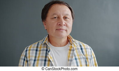 Portrait of Asian adult in casual clothing looking at camera...