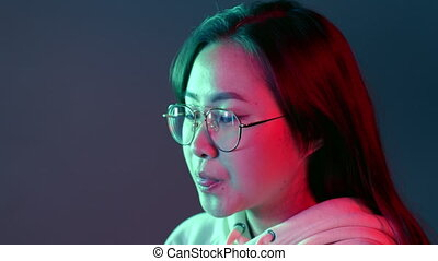 Portrait of asian beautiful girl with long hairstyle blows bubblegum, chewing gum in slow motion on studio background. Young woman in pink and green neon light.