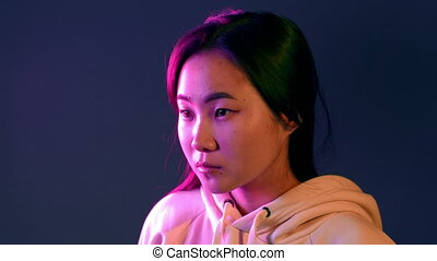 Portrait of asian beautiful girl with long hairstyle on studio background. Young woman in pink and violet neon light.