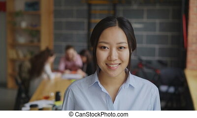 Portrait of asian confident businesswoman looking at camera and smiling while her multi-ethnic team working on start-up project in modern loft office
