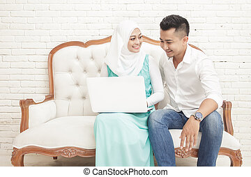 asian couple sitting on sofa while using laptop together