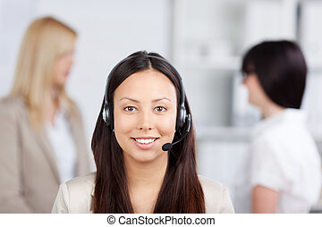 Portrait of Asian female customer service representative wearing headset with female coworkers in background in office