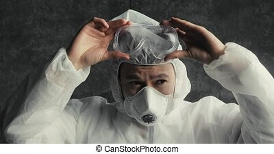 Human asian man doctor in protective clothes during coronavirus pandemic, portrait. Part of face in suit, mask and glasses on black background in clinic or hospital. Protection from epidemic concept.