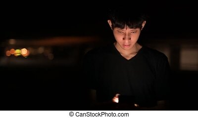 Portrait Of Asian Man Outdoors At Night In Parking Lot Using Mobile Phone
