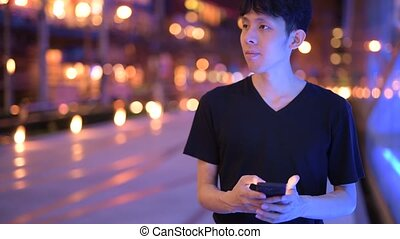 Portrait Of Asian Man Outdoors At Night Using Mobile Phone