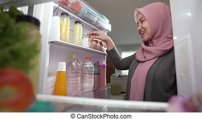 portrait of asian muslim woman open fridge door and getting ready to cook for dinner