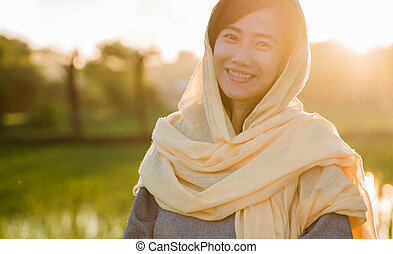 asian muslim woman with head scarf in the sunset
