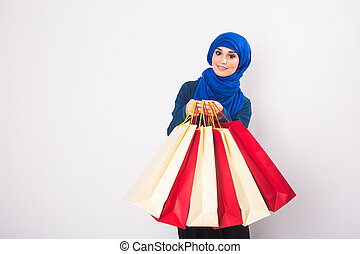 portrait of asian muslim woman with shopping bags on white background