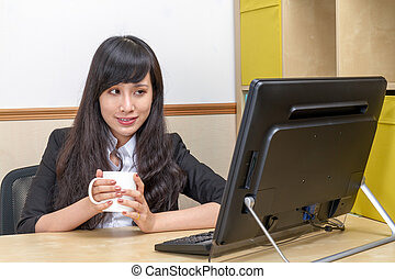 Portrait of Asian secretary sitting at desk