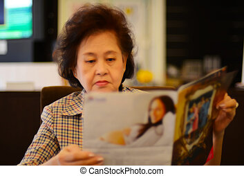 Portrait of asian senior woman reading newspaper