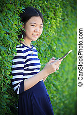 portrait of asian teen age ,girl with computer tablet in hand standing against green garden with happiness and relax emotion outdoor use for modern digital lifestyle