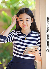 portrait of asian teen age girl with computer tablet in hand standing with happiness and relax emotion outdoor use for modern digital lifestyle