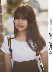 portrait of asian teenager standing outdoor with eye contact to camera