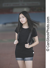 portrait of asian teenager wearing black t-shirt with backpack bag standing outdoor