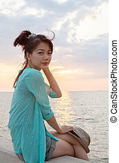 portrait of asian woman relaxing vacation holiday at sea side with sun set sky background