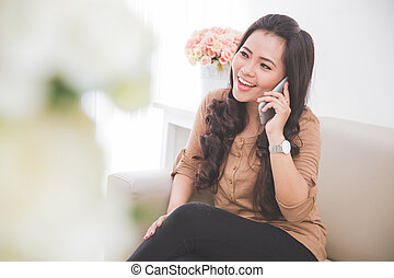 Woman sitting on a couch, calling friend with smartphone
