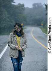 portrait of asian woman standing on mountain highway