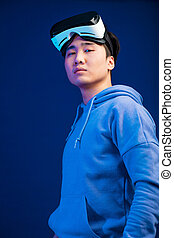 Portrait of Asian young man takes off his virtual reality glasses from his head.