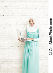 asian young woman wearing hijab standing while holding a laptop