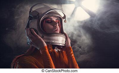 Portrait of astronaut girl in helmet, studio shot