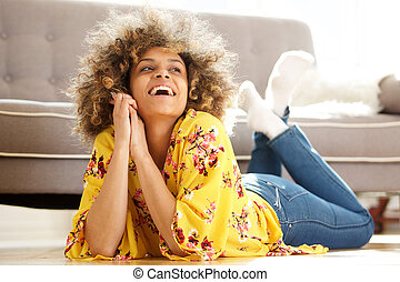 attractive african american woman lying on floor at home and laughing